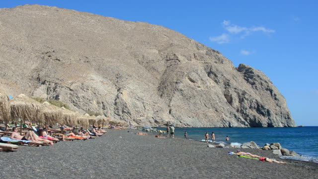 ws view of cyclades perissa famous black sand beaches and straw huts greek relax at beach / santorini, greece - insel santorin stock-videos und b-roll-filmmaterial