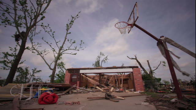 ws pan t/l view of damaged house, debris, basketball hoop and court / greensburg, oklahoma, usa - damaged stock videos & royalty-free footage
