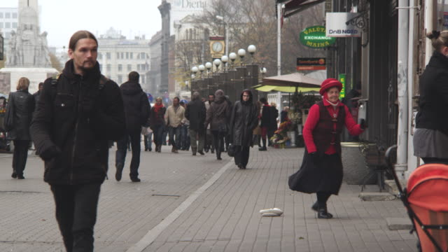 WS View of Dancing Street Performer with Pedestrians / Riga, Latvia
