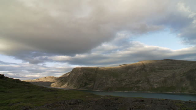 stockvideo's en b-roll-footage met ws view of dark clouds moving sky with large hills and river moving / torgat mtns, labrador, canada - wiese