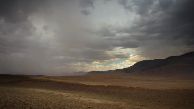 ws t/l td view of dark rain clouds moving over rugged terrain surrounding by distant mountains, glimpse of blue sky / wolwedans, windhoek, namibia - desert stock videos & royalty-free footage
