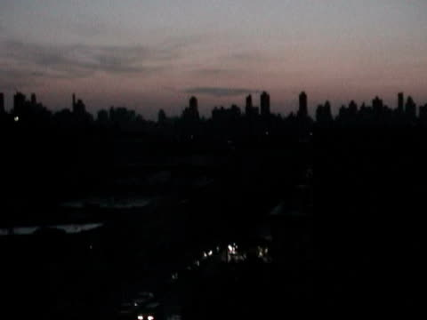 view of darkened manhattan skyline at dusk during citywide blackout on august 14 2003 / queens new york usa / audio - 2003 bildbanksvideor och videomaterial från bakom kulisserna