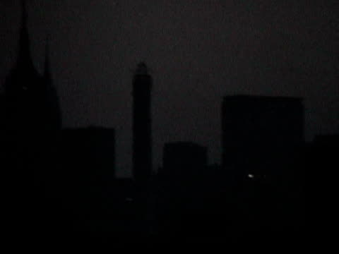 view of darkened manhattan skyline at night during citywide blackout on august 14 2003 / queens new york usa / audio - 2003 bildbanksvideor och videomaterial från bakom kulisserna