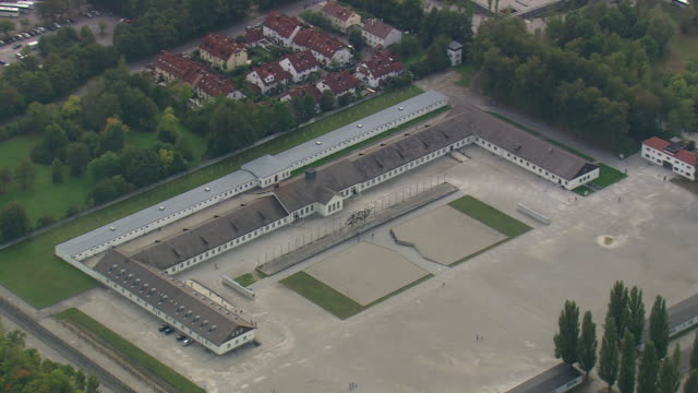 ws aerial zi view of darkest page of humanity at dachau concentration camp and houses / germany - konzentrationslager stock-videos und b-roll-filmmaterial