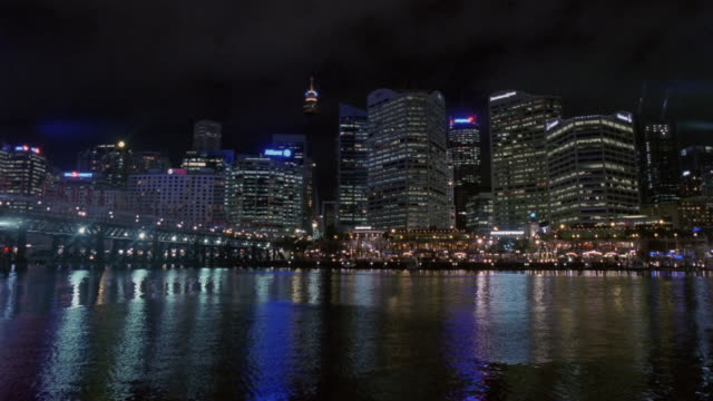 View of Darling Harbour wharf and skyscrapers in Central Business District at night / Sydney, Australia