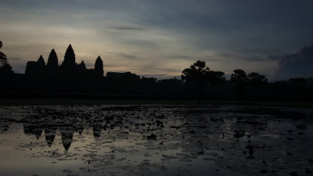 ws t/l view of dawn sky at angkor wat, clouds moving behind silhouetted temple with serene lake / hanoi, vietnam - angkor wat stock videos and b-roll footage