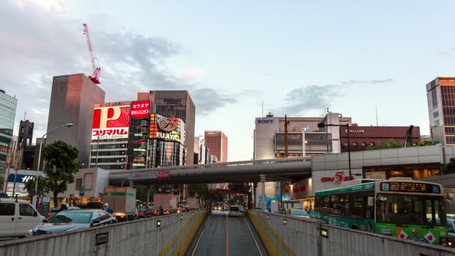 WS T/L View of day to night transition over busy crossing and tunnel in Ginza shopping area / Tokyo, Japan