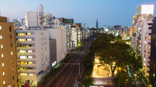 WS T/L View of day to night transition over shibuya area with train tracks from shibuya to harajuku stations and skatepark / Tokyo, Japan