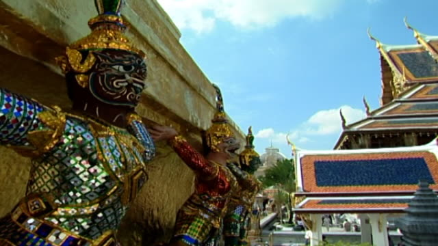 view of demon statues at the base of a golden chedi, or spire, and roofs adorned with golden chofas. - spire stock videos & royalty-free footage