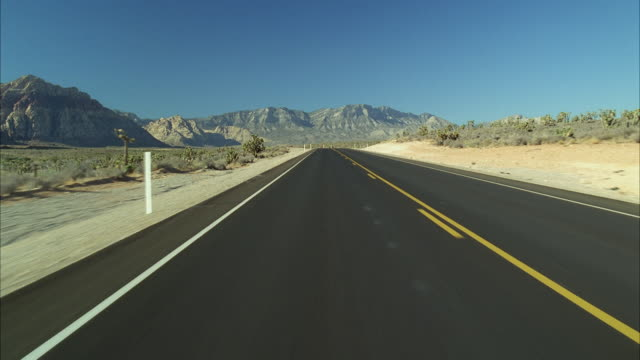 WS POV View of desert highway with mountains in background