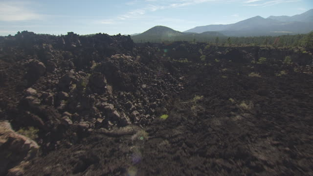 ws aerial pov view of desert landscape in sunset crater volcano national monument with mountains in background / flagstaff, arizona, united states - flagstaff arizona video stock e b–roll