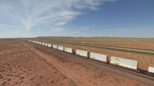 WS AERIAL POV View of desert landscape, with cargo train on track / Arizona, United States