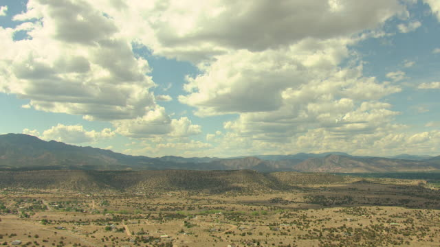 ws aerial view of desert landscape with green shrubs and mountain range under sun filled sky with large clouds in pueblo country / colorado, united states - pueblo colorado stock videos & royalty-free footage