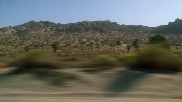 WS POV View of desert through moving car