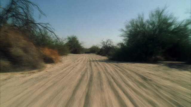 WS POV View of desert track from motorcycle