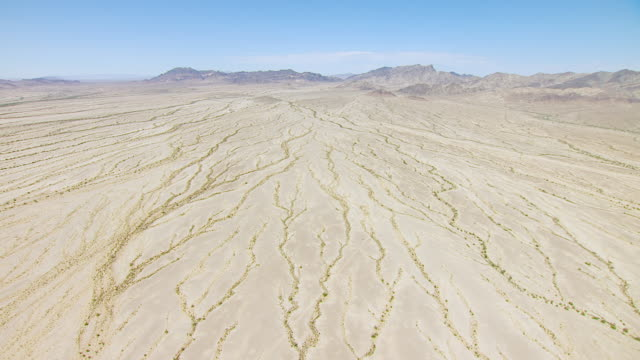 WS AERIAL POV View of Desert valley and dry stream beds with mountain ranges in background / California, United States