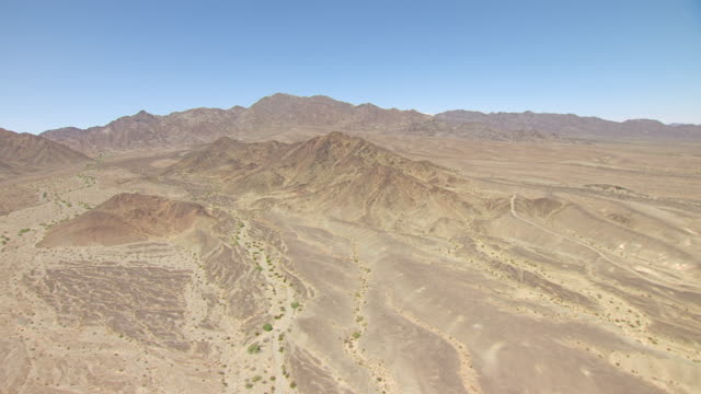 WS AERIAL POV View of Desert valley with foothills and mountain range in distance / California, United States