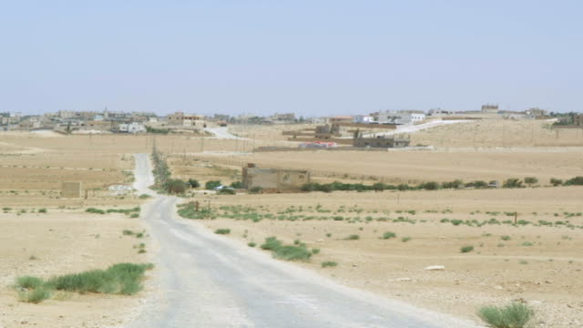 WS View of desert village with Humvee Passing on road / Desert Town, Jordan