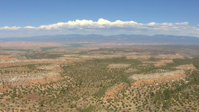 WS AERIAL PAN View of desert with clouds and mountains in Los Alamos County / New Mexico, United States