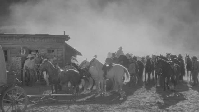 vidéos et rushes de ms view of desert with mountain range in group of people on horseback ride across terrain - culture des indiens d'amérique du nord