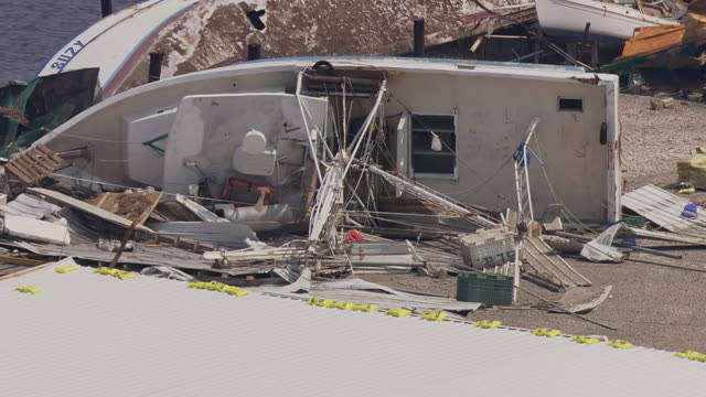 view of destructed warehouse and boats washed onto shore / united states - warehouse点の映像素材/bロール