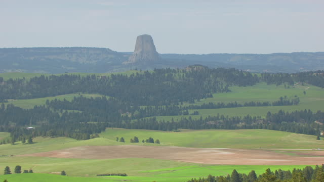 WS AERIAL View of Devils Tower with hillside trees / Wyoming, United States