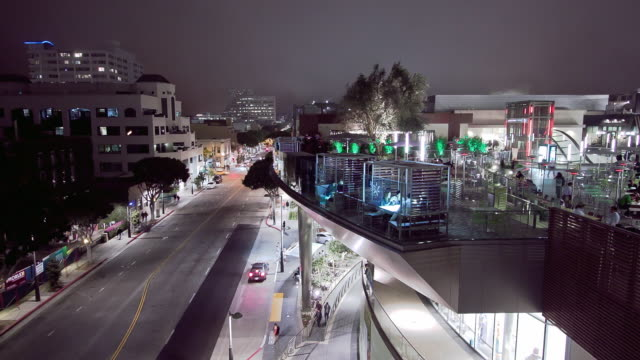 ws zi t/l view of dining deck on upper level of santa monica place shopping center overlooking city of santa monica at night as night fog rolls in from the ocean / santa monica, california, usa   - santa monica street stock videos & royalty-free footage