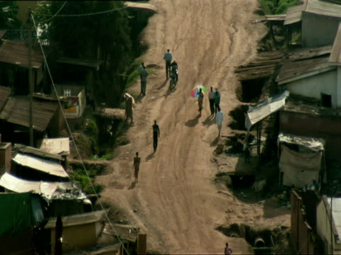 ws view of dirt road bordered by shacks in nyamirambo people walking on road / nyamirambo, kigali, rwanda - キガリ点の映像素材/bロール
