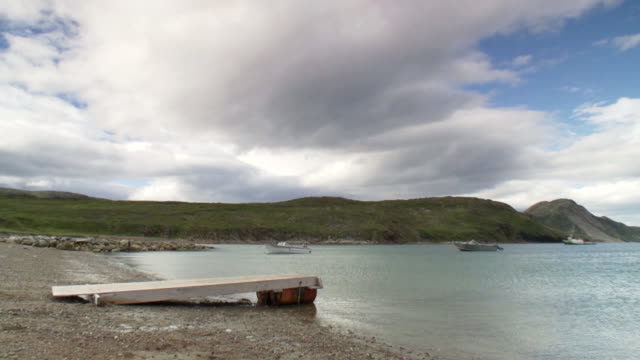 ws view of dock site with anchor boat floating in bay and covering hill line / torgat mtns, labrador, canada - wiese stock videos & royalty-free footage