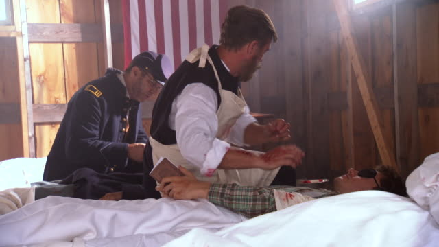 vidéos et rushes de ws view of doctor treating soldier with wounded arm then moves on to another patient / clear spring, maryland, united states - armée de l'union