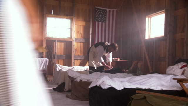 vídeos de stock e filmes b-roll de ws pan view of doctors and nurses moving around and treating wounded soldiers in field hospital / clear spring, maryland, united states - exército da união