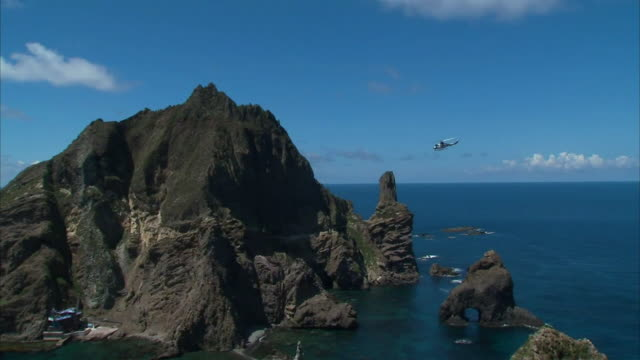 View of Dokdo island and one helicopter passing by (Dokdo is Korean islets located to east of Korean peninsula-Popular Destination)