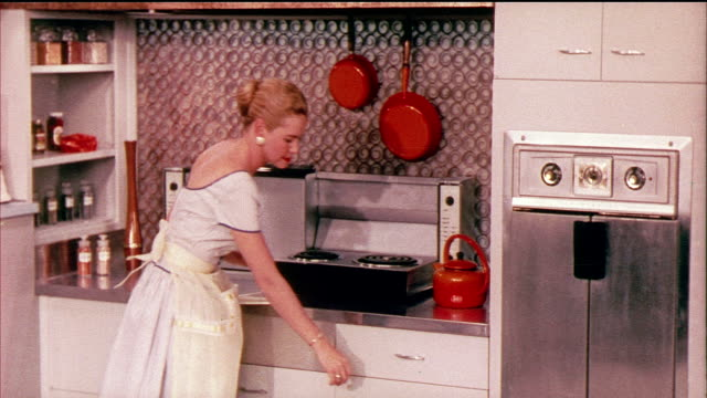 1958 MONTAGE MS PAN ZO View of domestic kitchen,  woman walking over to stove and pulling down section of burners / USA / AUDIO