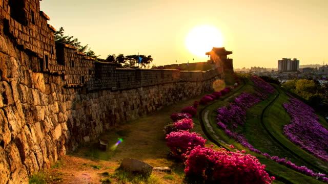 View of Dongbukporu bastion and Royal azalea of Suwon Hwaseong castle (Unesco World Heritage Site) at sunset