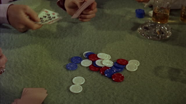 CU PAN View of Down poker chips and card on table hands