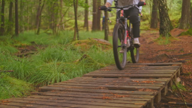 view of downhill riders over wooden bridge with mountainbikes in a pine forest in änggårdsbergen in gothenburg - non urban scene stock videos & royalty-free footage