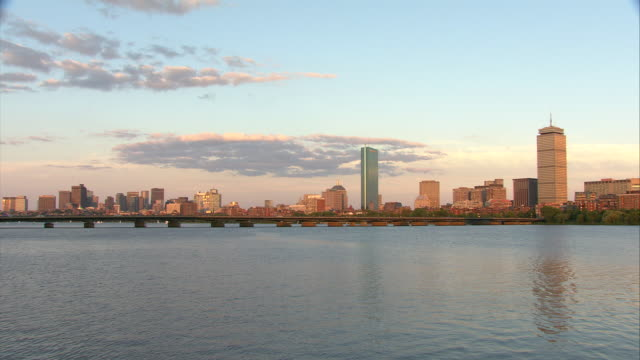 ws pan view of downtown boston across charles river with harvard bridge, prudential tower and hancock tower in distance / boston, massachusetts, usa - harvard bridge stock videos & royalty-free footage
