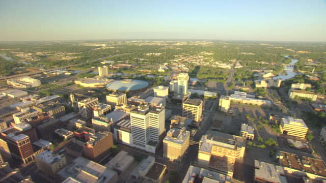 vídeos de stock e filmes b-roll de ws aerial td view of downtown buildings during sunrise and arkansas river / wichita, kansas, united states - kansas