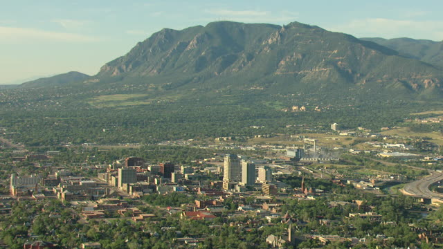 WS DS AERIAL View of downtown buildings with mountains covered in trees / Colorado Springs, Colorado, United States