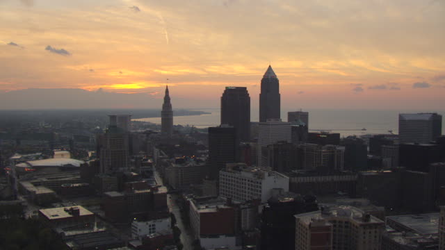 ws aerial view of downtown buildings with sunset and lake erie / cleveland, ohio, united states - cleveland ohio stock videos and b-roll footage