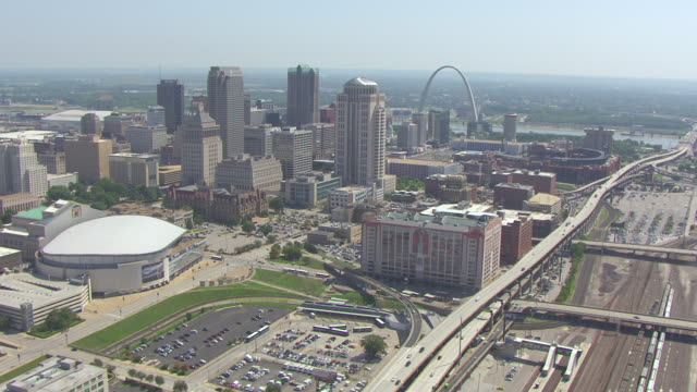 ws aerial view of downtown flying east towards gateway arch and busch stadium and mississippi river / st louis, missouri, united states - 西方拡大点の映像素材/bロール