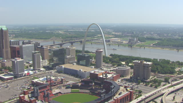 WS AERIAL View of downtown flying east towards Gateway Arch and Busch Stadium and Mississippi River / St Louis, Missouri, United States