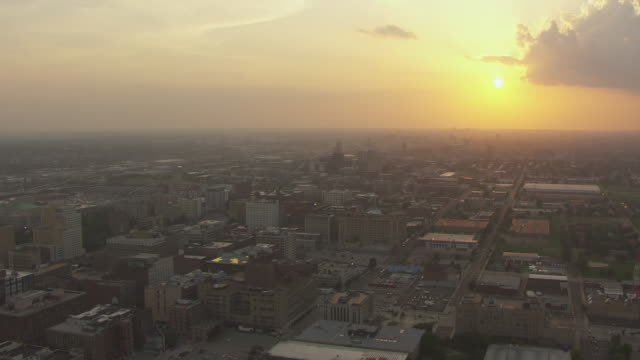 WS AERIAL View of downtown flying west towards setting sun on horizon / St Louis, Missouri, United States