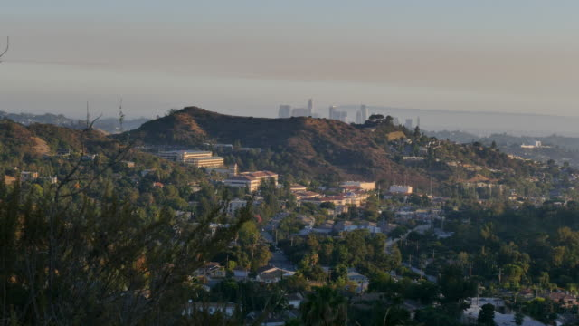 view of downtown los angeles from suburban hills a pink haze hangs over the city - glendale california stock videos & royalty-free footage