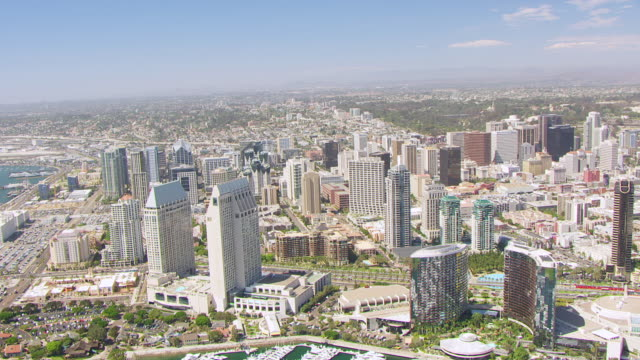 ws aerial pov view of downtown san diego along the bay marina and convention center in foreground with rocky hills in hazy distance / san diego, california, united states - san diego stock-videos und b-roll-filmmaterial