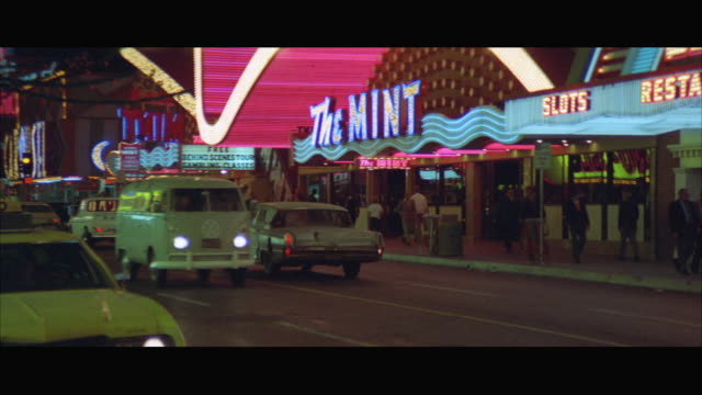 vídeos de stock, filmes e b-roll de ms pan view of downtown street with cars moving besides restaurants at night / las vegas, nevada, usa - 1973