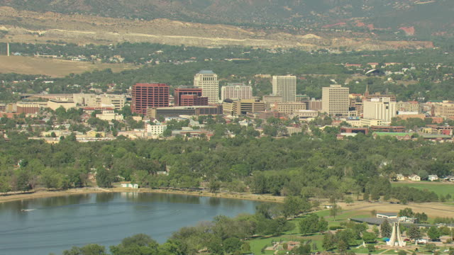 WS AERIAL View of downtown with mountains and buildings with green trees surrounding / Colorado Springs, Colorado, United States