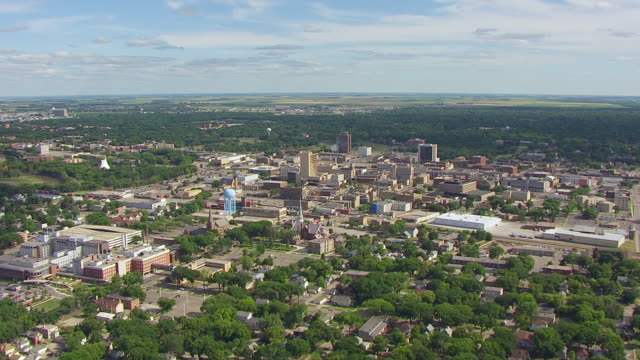 WS AERIAL View of Downtown with train traveling through town at Northern Pacific Railway Depot / Fargo, North Dakota, United States