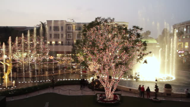 PAN MS View of  dramatic fountain with illuminated dancing waters at dusk to reveal giant Christmas tree in shopping center exterior / Glendale, California