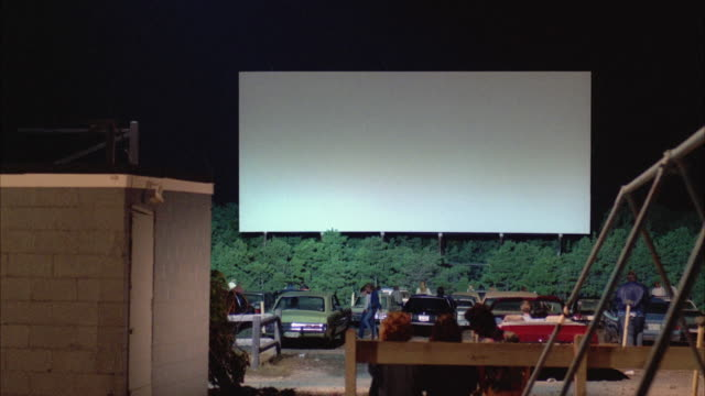 ws view of drive-in theater screen with cars in foreground - projection screen stock videos & royalty-free footage